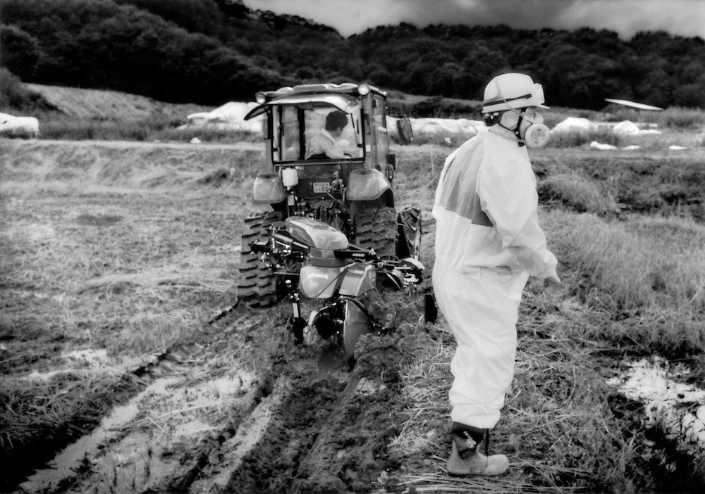 Farmer in hazmat suit and mask to protect him from radioactive fallout in the soil looks out over field undergoing decontamination.  Contaminated soil is packed into large sacks and stored under white tarpolins.  On the Tomioka Highway, between Tsushima and Yamakiya, Fukushima Prefecture, Japan.