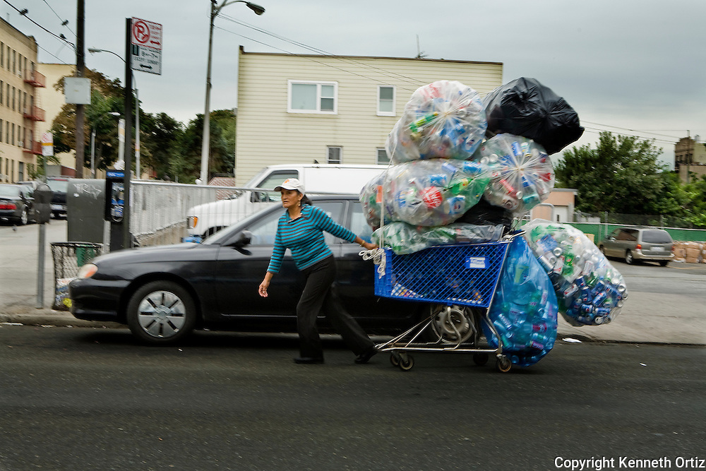 An immigrant woman hauls a shopping cart full of recyclable soda and beer cans up Broadway in Astoria Queens.
