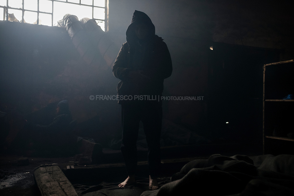 An Afghan is seen while praying in a warehouse where he is living in extreme condition.