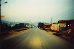 Long straight road through small countryside town lined with substandard dwellings, Northern Laos, Southeast Asia