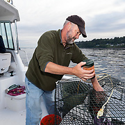 WA11860-00...WASHINGTON - Lee Hamilton pilots the boat as Jim Johansen loads a bait tube into a shrimp pot while fishing on the Puget Sound. (MR# J5-H14)