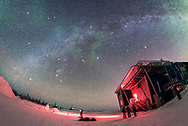 The winter Milky Way and constellations, to the south over the Churchill Northern Studies Centre, near Churchill, Manitoba, on a very clear night on January 25, 2017. A few bits of green aurora are visible. People from the tour group and staff are outside enjoying the stars and a developing aurora to the north behind the camera.<br /> <br /> This is with the 12mm Rokinon full-frame fish-eye lens at f/2.8 and for 30 seconds at ISO 3200 with the Nikon D750.