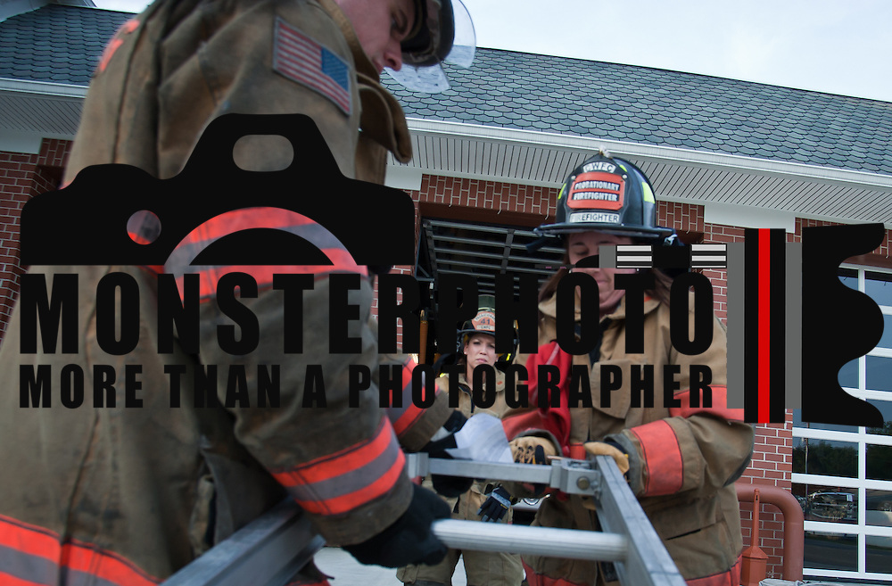 Lieutenant Maddy Cooper (left) observe Camden-WyomingFire fighter Maria Payne (right) as Payne open hooks on top of a 24 foot ladder during ladder training Wednesday, July 6, 2011, in Camden-Wyoming Delaware.