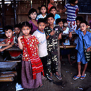 """Schoolchildren inside the refugee school in Mae La. Burmese refugee camp """"Mae La"""" is north of border-town Mae Sot and lies along the Thai-Burmese border on the side of Thailand. Approximately 50,000 people live there. 38,167 was the official number of registered people in November 2009, according to the Thailand Burma Border Consortium (TBBC), and the rest are unregistered or people who come and go."""