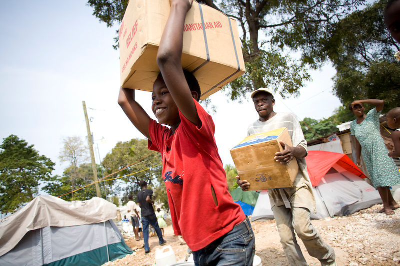 Nicholas Mardoché carries a case of canned meat from a delivery truck to a storehouse in the camp where he lives. The camp is named Galilee,  Port Au Prince, Haiti. Photo by Ben Depp 3/3/2010