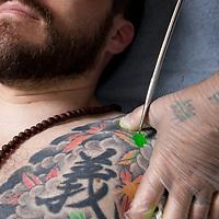 Horiyoshi III (the 3rd) (out of pic), expert Japanese tattooist, tattoos on the body of his German understudy Alex Reinke (also known as Horikitsune), in Horiyoshi's studio in Yokohama, Japan, on Saturday 10th September 2011.