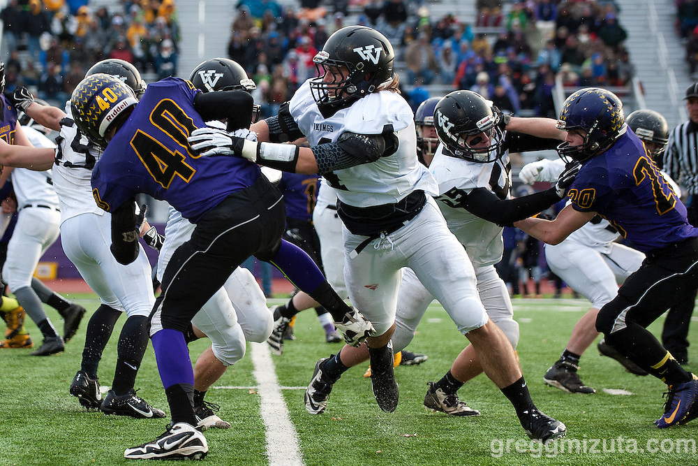 Vale junior Zac Jacobs looks for running room behind the blocks of Andrew Weber on Joey Knox and Michael Young on Hunter Knox during the first quarter of the Oregon 3A State Championship game at Kennison Field, Hermiston, Oregon, November 29, 2014. Vale defeated Harrisburg 45-19 to end the season with a 12-0 record and Vale's 11th state football title.<br /> <br /> Jacobs finished with two touchdowns and 175 all purpose yards including 142 rushing yards on 18 carries, 11 yards receiving on 2 receptions, and one kickoff return for 19 yards.