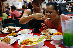 Aishah's older son Jafni help her with her food in a food court after practices at an air rifle range in Singapore, 11 June 2014. Everyday life is still a struggle for her though. Simple tasks like brushing her teeth still requires help from a domestic helper and her prosthetics hands are still not dexterous enough for handling forks and knives to feed herself.