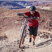 SHOT 10/15/16 4:29:48 PM - Doug Starkey of Steamboat Springs, Co. pushes his bike uphill during a climbing section along the White Rim Trail. The White Rim is a mountain biking trip in Canyonlands National Park just outside of Moab, Utah. The White Rim Road is a 71.2-mile-long unpaved four-wheel drive road that traverses the top of the White Rim Sandstone formation below the Island in the Sky mesa of Canyonlands National Park in southern Utah in the United States. The road was constructed in the 1950s by the Atomic Energy Commission to provide access for individual prospectors intent on mining uranium deposits for use in nuclear weapons production during the Cold War. Four-wheel drive vehicles and mountain bikes are the most common modes of transport though horseback riding and hiking are also permitted.<br /> (Photo by Marc Piscotty / &copy; 2016)