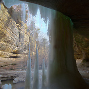 Water drips and ice falls from the cave behind LaSalle Canyon Falls as it begins to thaw in late winter in Starved Rock State Park near LaSalle, Illinois. The 20-foot (6-meter) waterfall can completely freeze in winter. Here, part of the icefall has melted as is once again flowing as a waterfall.