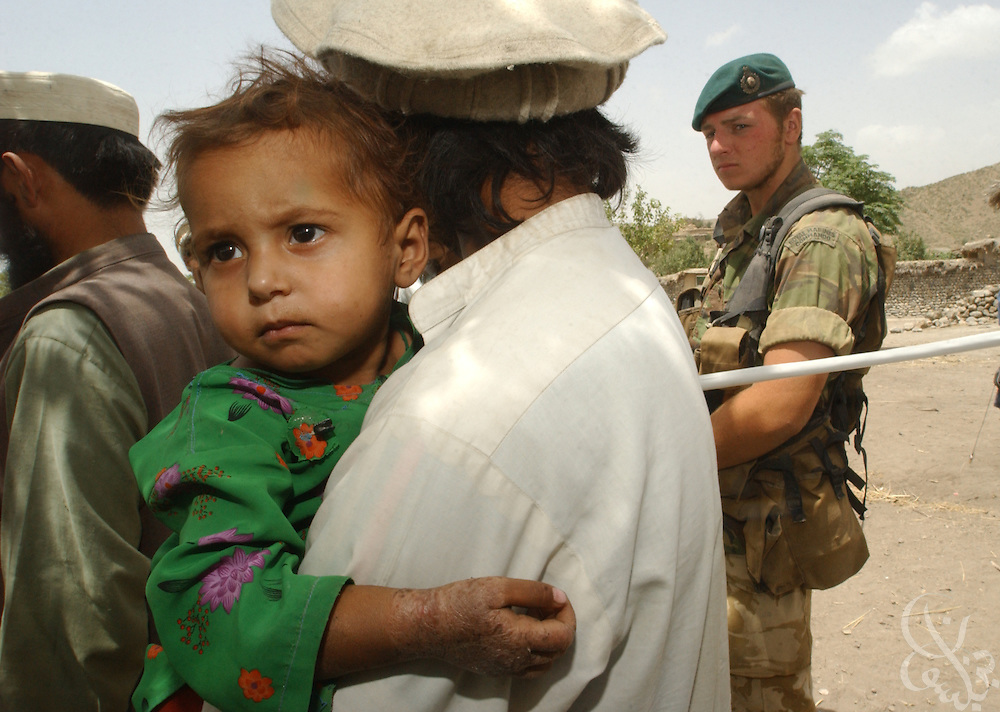 A British Royal Marine Commando stands guard as Afghans line up for treatment during a joint US-UK  medical mission June 18, 2002 at a remote village in southeastern Afghanistan.