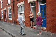 UK. Manchester. Salford. The Langworthy area of Salford where a new £15m development called Chimney Pot Park is being developed amongst  the boarded up areas..Pat and Walter Gowenlock outside their old home on Cooperative Street in the Langworthy area of Salford. They were forced out by the council after living there for 40 years. They accepted £10,000 to move on. Later the demolition plans were shelved, the council put in new tenants. .Photo shows Pat and Walter meeting the current occupier, John Houghton..Photo©Steve Forrest/Workers Photos