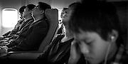 Passengers, including three Japanese businessmen, sleeping on aircraft.