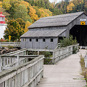 Irish River or Vaughan Creek #1 Covered Bridge was built in 1935 in picturesque St. Martins, in Saint John County, New Brunswick, Canada. The lighthouse building was built in 1983 to display the lantern room from the 1883 Quaco Head Lighthouse and to serve as a Visitor Information Center in St. Martins. Climb to the lantern to view the harbour and two historic covered bridges. Observe the extreme tides of Bay of Fundy lifting fishing boats near the bridge. Drive through the covered bridge and go 7 km on Big Salmon River Road to reach the start of the Fundy Trail Parkway, a 16 kilometer auto route along the Fundy coast ending at Big Salmon River, a former lumbering center. Bay of Fundy has the highest tidal range in the world, due to a resonance of being just the right length (270 km) matching the gravitational pushing cycle of the Moon that causes the tides. Coincidentally, the time it takes a large wave to go from the mouth of the bay to the inner shore and back is practically the same as the time from one high tide to the next. (You can see the effect of resonance for yourself by steadily pushing a long pan of water back and forth: an optimal pushing frequency for a given pan length will build up a high wave of water which sloshes out; but pushing too fast or too slow won't build up the big wave.) Two high tides occur per day, one when the ocean side is nearest the Moon, and one on the side of the Earth most distant from the Moon, about 12 hours and 25 minutes from one high tide to the next. The Bay of Fundy is on the Atlantic coast of North America, on the northeast end of the Gulf of Maine between the Canadian provinces of New Brunswick and Nova Scotia. St. Martins (2006 population: 386) is 40 km east of Saint John. St. Martins (originally known as Quaco) was founded by Loyalists in 1783. Its important 1800s shipbuilding center faded, leaving tourism as today's major industry.