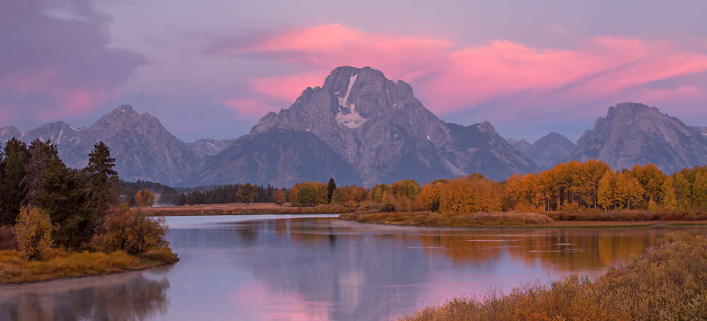 In the stillness of the predawn hours, the sky takes on a pinkish hue above Mount Moran in Grand Teton National Park.