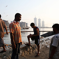 Fisherman chat after returning to port as construction continues (in the background) on buidlings in the financial district in Manama, Bahrain, Wednesday, September 9, 2009. At back is a traditional boat. There is a great clash of values taking place in Bahrain, as it has throughout a region where fabulous oil wealth and the intoxicating influence of globalization have often overwhelmed heritage and tradition. September 2009.