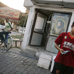 Havdar Fareed, 14, sells refreshments along the road in Baghdad, Iraq, July 23, 2003. With two brothers who were Fedayeen before the war, Fareed was trained by the Saddam Hussein regime in a military camp so he could also become a Fedayeen fighter.