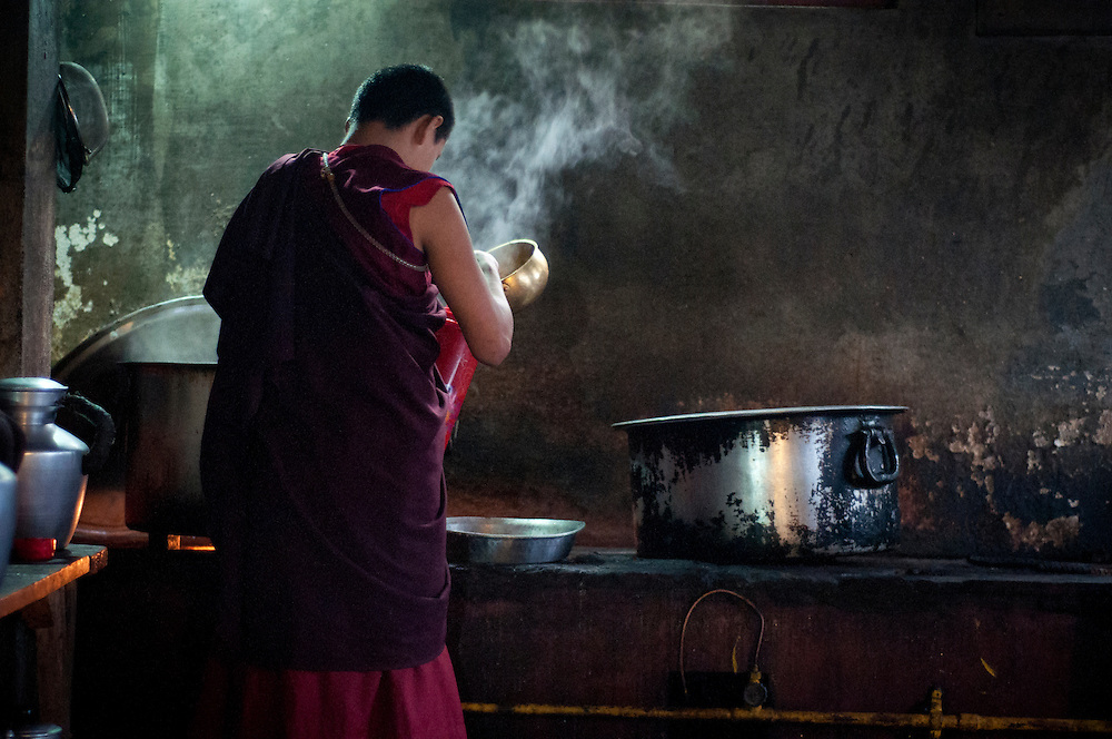 Lunchtime in a monastery kitchen; a monk pours himself a bowl of steaming soup.