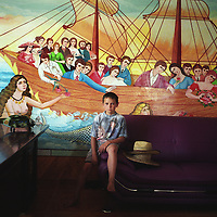AIonut, a young Roma boy,  sits below a mermaid /nautical painting on the wall of his families home, in the new part of the Sintesti Roma camp. Nautical scenes are very popular as wall decoration, but no-one within the camp knows the reason why they were first painted.