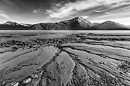 Channels in the silt of Turnagain Arm created by low tide  with the Kenai  Mountains in the background near Portage in Southcentral Alaska. Summer. Evening.