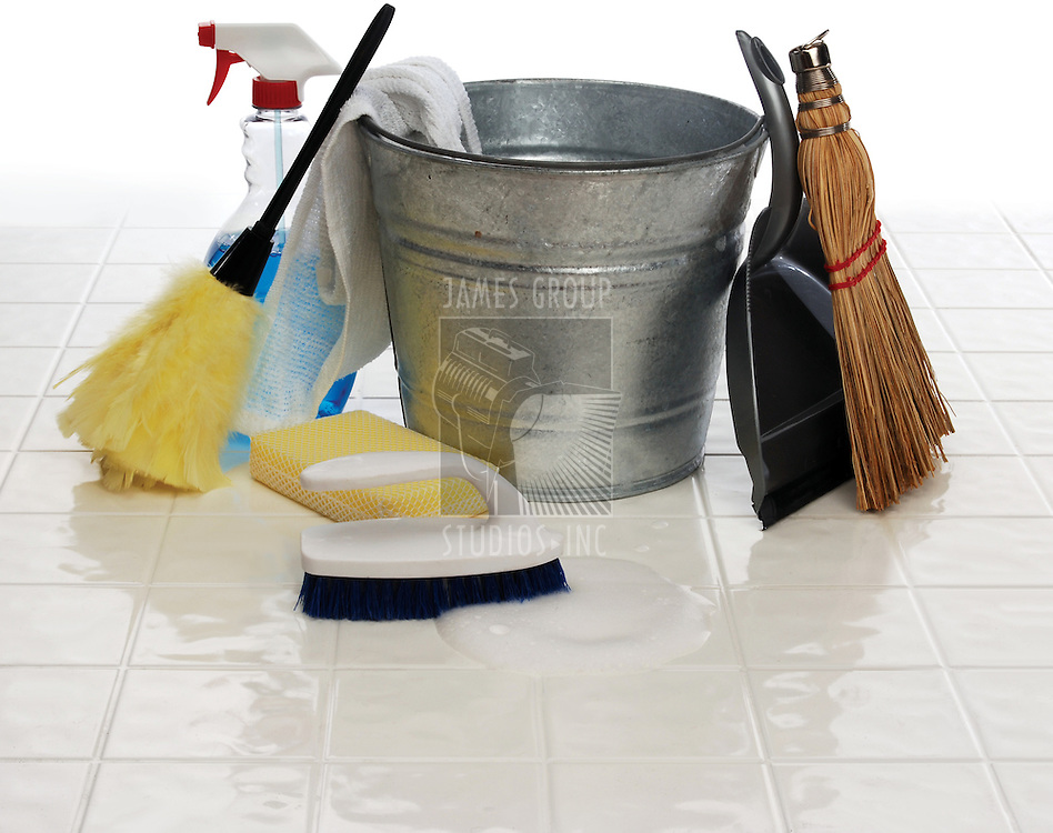 cleaning supplies: spray bottle, broom, duster, wash cloth, scrub brush, bucket, dust pan on white tiles