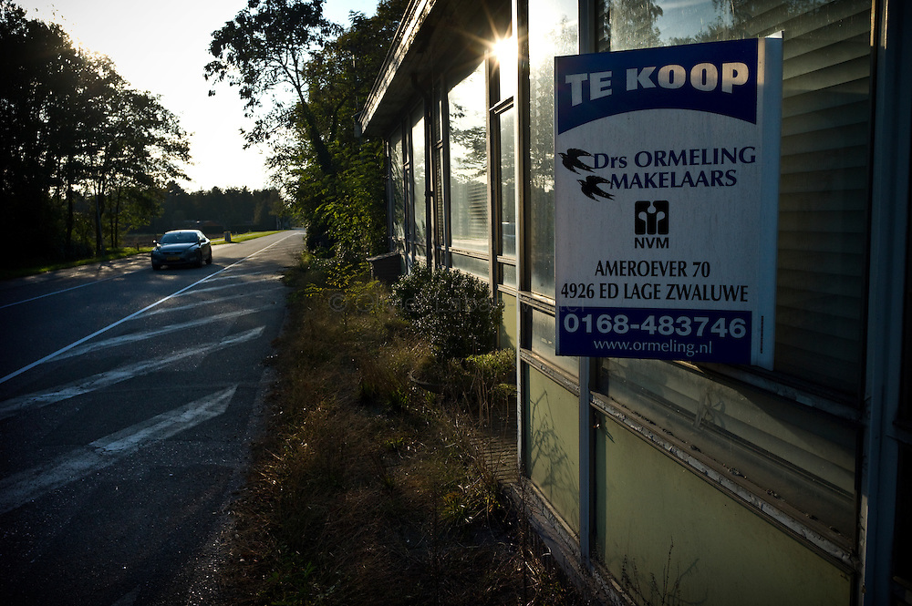 Le 21 octobre 2011, frontière Pays-Bas / Belgique, près de Reusel (NL), RN 284. Une voiture passe devant l'ancien poste frontière désormais à l'abandon et en vente. Sur le panneau est écrit «à vendre».