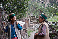 Two Kinnauri women visit at the end of a day of working in the fields in the village of Giabong in the Ropa Valley of Himachal Pradesh, India.
