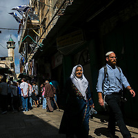 A Palestinian woman walks next to an Israeli man along&nbsp;Hagai&nbsp;Street&nbsp;in Jerusalem's Old City , Thursday, Oct. 8, 2015. The tension on the street has been rising steadily for several years now, particularly in the alleys leading off it to the Temple Mount. That is where Muslim women gather to curse Jews on their way to the Temple Mount and where closely-guarded groups exiting the Western Wall tunnels make their way back to the Western Wall concourse. It is where hundreds of ultra-Orthodox pass on their way to the Western Wall and where hundreds of tourists gather while walking the Via Dolorosa. The street is also one of the two main markets of the Muslim Quarter.<br /> Photo by Olivier Fitoussi.