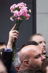 Old Compton Street, Soho, London, June 13th 2016. Thousands of LGBT people and their friends converge on Old Compton Street in London's Soho to remember the fifty lives lost in the attack on gay bar Pulse in Orlando, Florida. PICTURED: Pink carnations are held aloft as thousands remember the victims in Orlando.