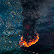 A plume of smoke rises from a burn of collected oil, May, 2010. A total of 411 controlled burns were used to try rid the Gulf of the most visible surface oil leaked from the BP Deepwater Horizon.