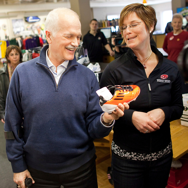 NDP leader Jack Layton shares a laugh with Webco Sports owner Cindy Weber after finding a soccer shoe with NDP orange during a campaign stop at her store in Kitchener, Ontario, March 29, 2011. Earlier in the day Layton announced his plan to limit credit card fees for consumers and small businesses.<br /> AFP/GEOFF ROBINS/STR