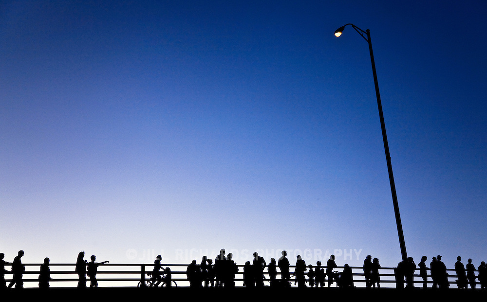 A crowd of people, families and pedestrians gather to the Congress Avenue Bridge in downtown Austin, TX for a better view of the bats that fly out from under the bridge. <br /> <br /> A crowd of people in silhouette against a blue sky at dusk under a single street light.