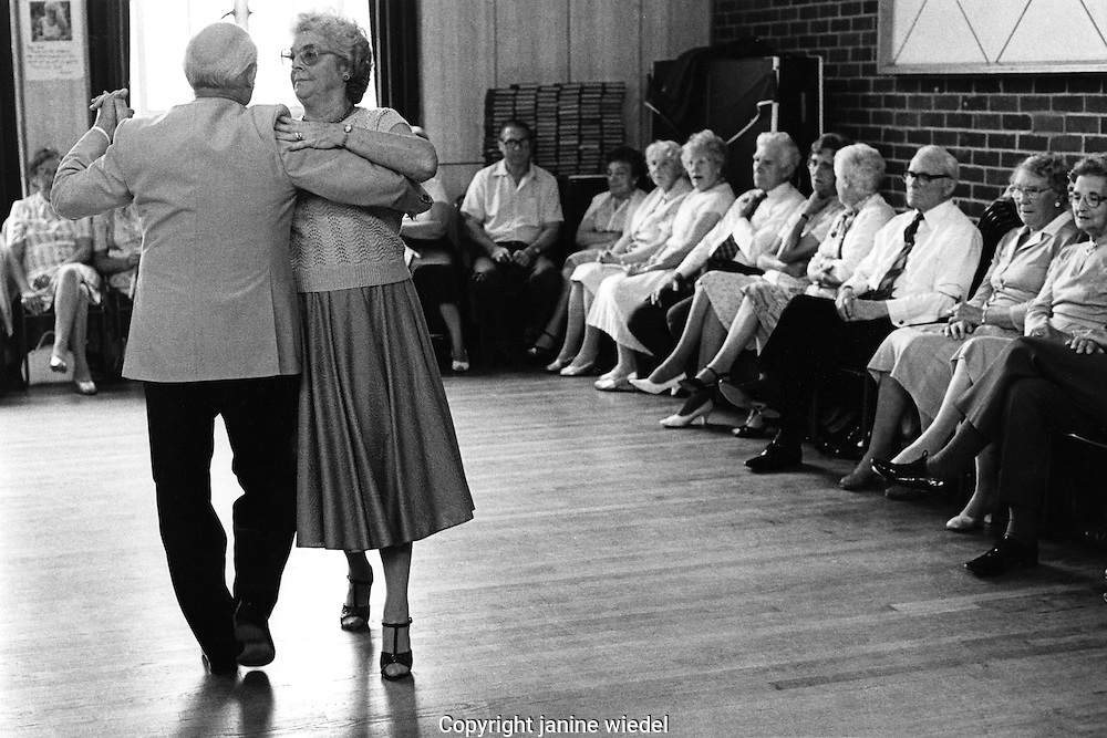 Couple demonstrating new dance steps at afternoon tea dance in small town.