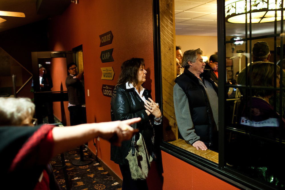 People in an overflow area watch through a window as Republican presidential candidate Mitt Romney meets with voters at the Stoney Creek Inn on Saturday, December 31, 2011 in Sioux City, IA.