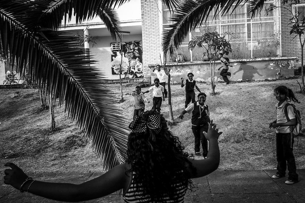 Children play tag outside of the Sarria nucleo, of the El Sistema music program in Sarria, a  dangerous slum in Caracas, Venezuela.