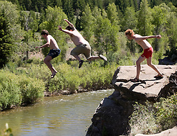 NEWS&GUIDE PHOTO / PRICE CHAMBERS.From left, Matt Leitch, Jeff Senna and Jordan Sjol leap from a cliff above the Gros Ventre River on Thursday. The group spent the afternoon hanging out on the rocks and occasionally jumping about 25 feet down to the chilly water below.