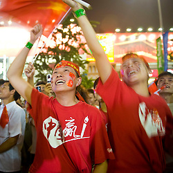 Chinese girls wait to see the closing ceremony in a commericial zone during the Beijing 2008 Olympic Games August 24, 2008 in Beijing, China. Ami Vitale