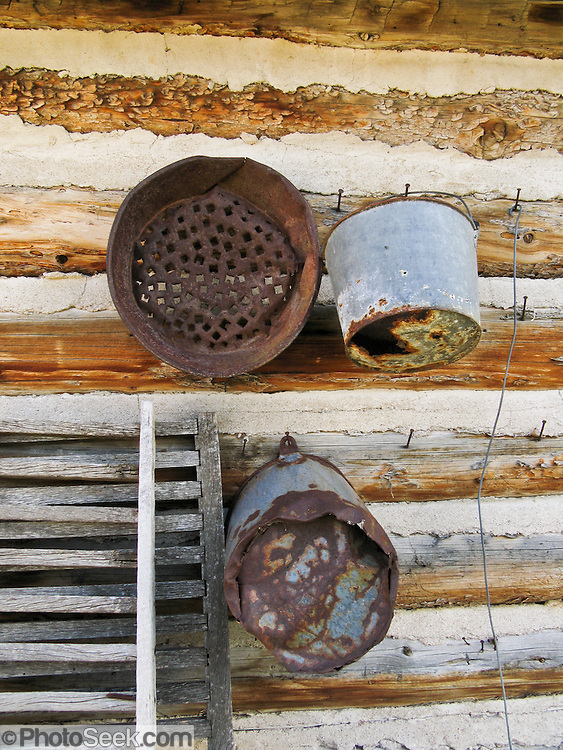 """Old buckets hang on a late 1800s restored frontier log cabin in Nevada City, Montana, USA. Nevada City was a booming placer gold mining camp from 1863-1876, but quickly declined into a virtual ghost town. This fascinating town inspires you to imagination what life must have been like in early Montana when gold was discovered at nearby Alder Gulch. More than 90 buildings from across Montana have been gathered for preservation at Nevada City, mostly owned by the people of the State of Montana, and managed by the Montana Heritage Commission. In 2001, the excellent PBS television series """"Frontier House"""" used one of the buildings and its furnishings to train families in re-creating pioneer life. A miner's court trial and hanging of George Ives in the main street of Nevada City was the catalyst for forming the Vigilantes, a group of citizens famous for taking justice into their own hands in 1863-1864. Directions: go 27 miles southeast of Twin Bridges, Montana on Highway 287."""