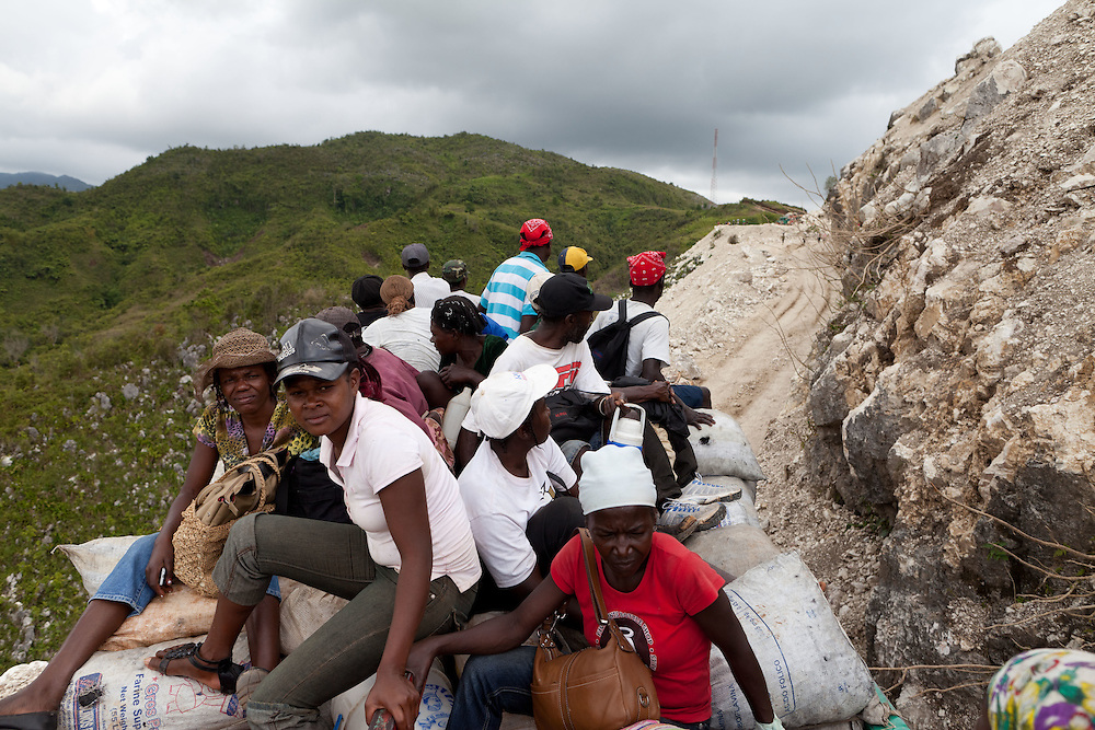 Men and women on top of their sacks of vegetables fruit and charcoal on a truck heading from the rural town of Duchity to Port-Au-Prince. The Inter-American Development Bank is funding a road project in the south of Haiti, aiming to cut travel time and transportation costs, and to improve living conditions in the southern provinces. This 50-mile stretch of road connects the small cities of Les Cayes and Jeremie and many rural villages in between. A Brazilian company, OAS, is doing the construction. The road is far from complete, but is already transforming commerce and daily life in the area. Travel time has been cut in half; fewer trucks are breaking down, so less food is spoiled; and farmers are planting more crops in anticipation of more dependable farm-to-market transportation.