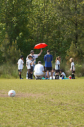 coach holds red umbrella to provide shade at time out of youth soccer league players, Richmond, VA