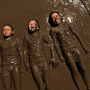 "Amanda Murphy, left, Emily Peterson, center, and Kathleen Conforti, all 9, play in a giant mud pit at ""Mud Madness"" at the riverwalk pavillion in Naperville, Ill."