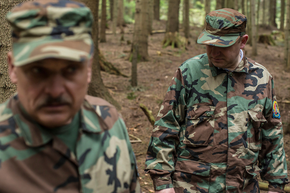 SKOLE, UKRAINE - MAY 1, 2015: Volodymyr Kharchuk, left, and Svyatoslav Sheremeta, deputy director and director of the organization Dolya, respectively, in the forest among World War II-era mass graves believed to contain the remains of Ukrainian partisans in Skole, Ukraine. Dolya was formed to excavate and repatriate remains from World War II, though its focus is often on locating the graves of Ukrainian partisans killed by Soviet forces. CREDIT: Brendan Hoffman for The New York Times