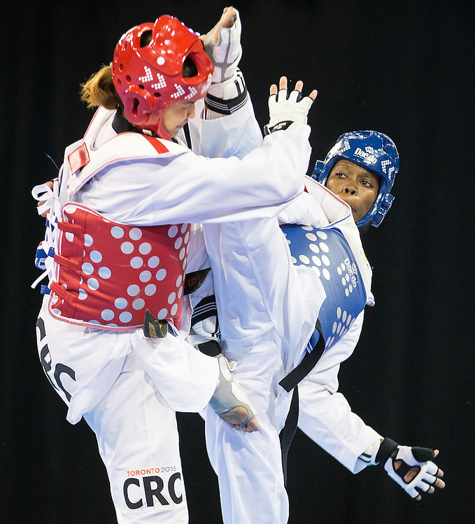Daima Villalon (R) of Cuba lands a kick to the head of Katherine Alvarado of Costa Rica during their bronze medal contest in women's taekwondo -67 kg division at the 2015 Pan American Games in Toronto, Canada, July 21,  2015.  AFP PHOTO/GEOFF ROBINS