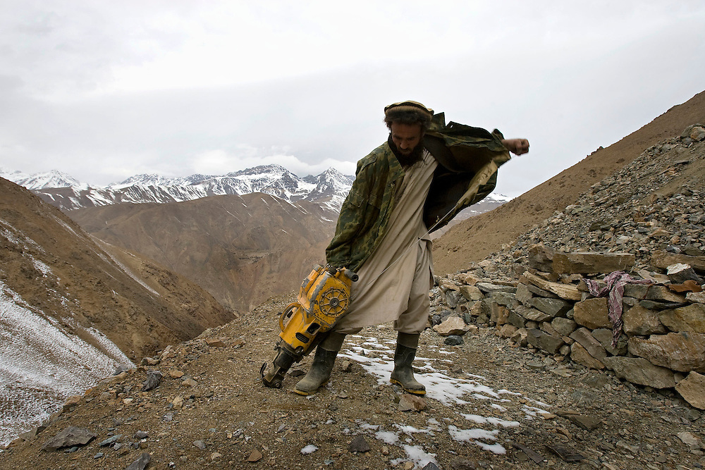 An emerald miner attempts to start a pneumatic drill high in the mountains of the Panjshir, Afghanistan on the 15th December 2008.