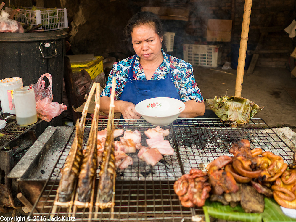 11 MARCH 2016 - LUANG PRABANG, LAOS:  A woman grills fish and chicken in the market in the community of Chomphet, across the Mekong River from Luang Prabang. Laos is one of the poorest countries in Southeast Asia. Tourism and hydroelectric dams along the rivers that run through the country are driving the legal economy.      PHOTO BY JACK KURTZ