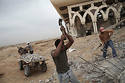 Stone collectors break apart rubble beside the main terminal building of Yasser Arafat International Airport in southern Gaza. The airport was destroyed by Israeli warplanes in 2001 and 2002, and has become a source of building materials for much needed  reconstruction in Gaza.