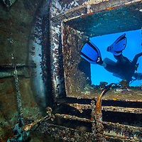 Female scuba diver exits hatch of El Águila wreck; West End, Roatan, Honduras