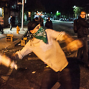 WASHINGTON, USA - APRIL 27: A protestor throws a liquor bottle at police lines during riots in Baltimore, USA on April 27, 2015. Protests following the death of Freddie Gray from injuries suffered while in police custody have turned violent with people throwing debris at police and media and burning cars and businesses.