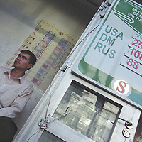 Currency exchange bureau sits within his office awaiting customers, outside a board display exchange rates, in Dushanbe, Tajikistan.