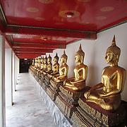 Row of Buddha statues at Wat Pho temple in Bangkok, Thailand. Golden!
